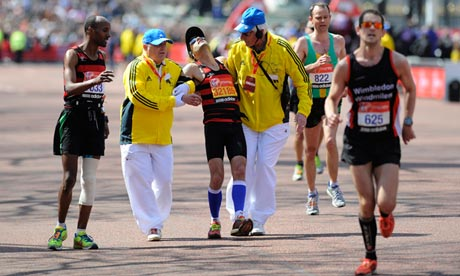 Exhausted runner helped towards the finishing line at the 2013 London Marathon