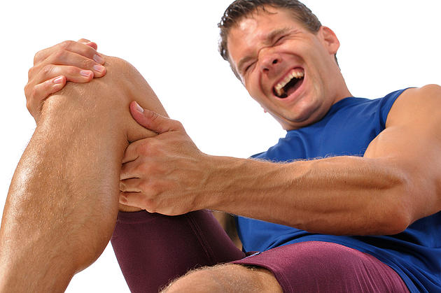 Male athlete on floor clutching knee and hamstring in excrutiating pain on white background